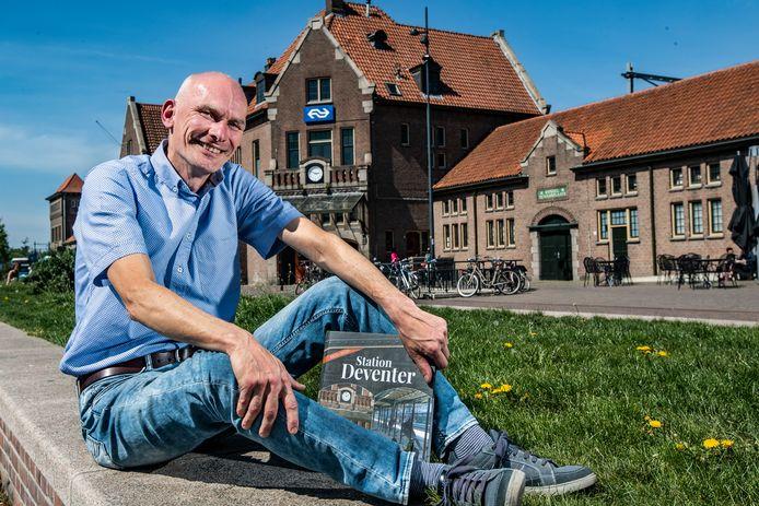 Auteur Arno Dijkhof voor het station in Deventer waar hij honderd jaar na de opening een  fraai boekwerk schreef.