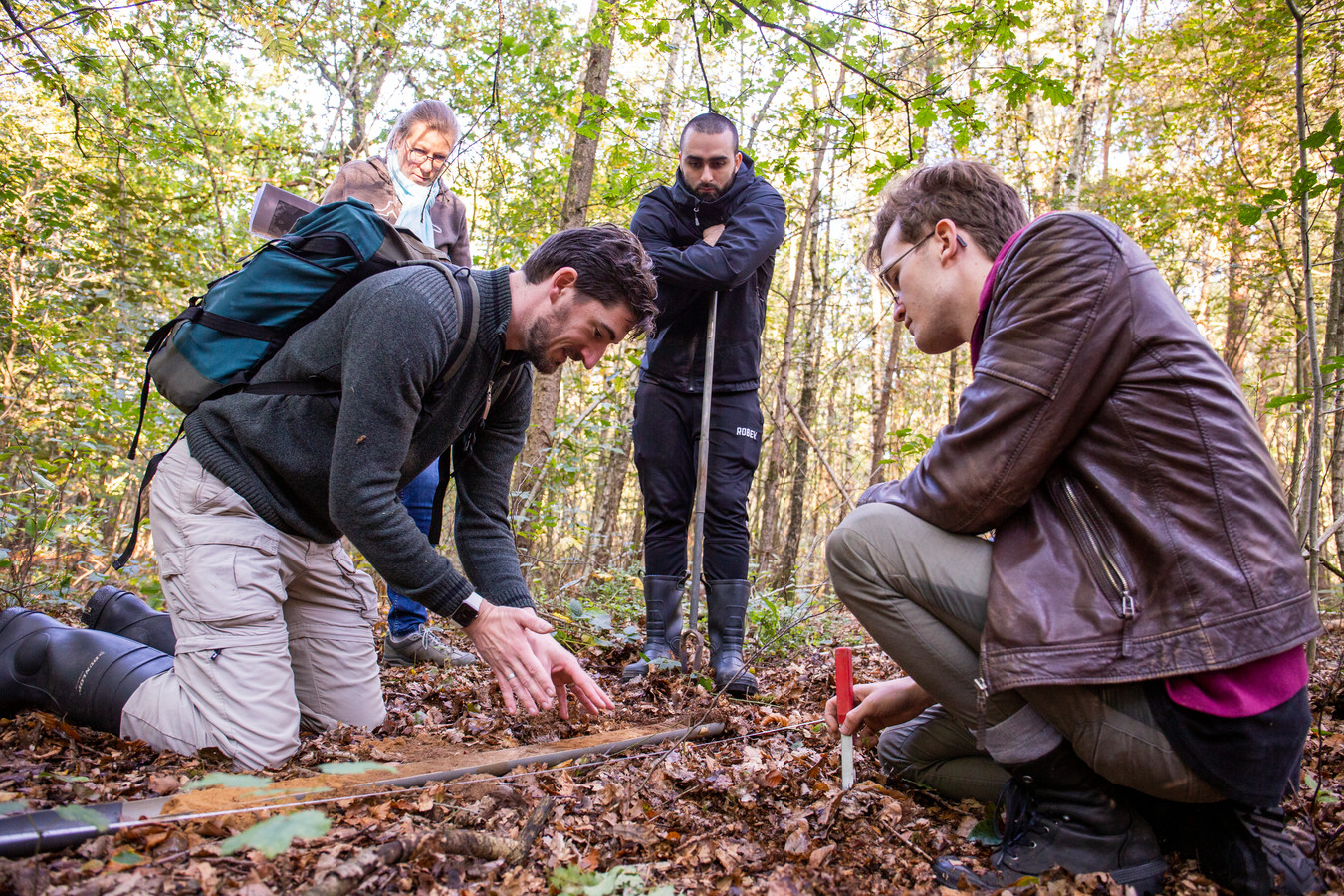 Projectleider Wouter Verschoof-van der Vaart van de Universiteit Leiden bekijkt het bodemprofiel dat is opgeboord. Mert Pasman (midden) en Jonathan Otten (rechts) kijken toe. Achteraan vrijwilligster Marjon Kruissink.