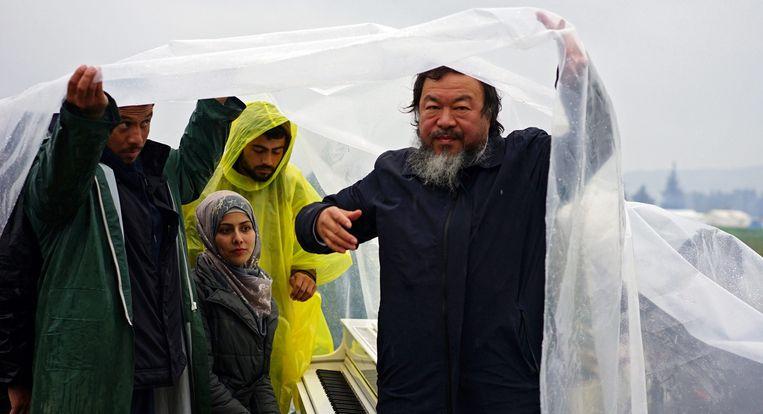 Ai Weiwei plant een spierwitte vleugelpiano in de modder, in een vluchtelingenkamp op de grens van Griekenland en Macedonië. Beeld epa