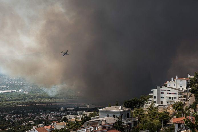 Archiefbeeld ter illustratie. Een blusvliegtuig vliegt boven een bosbrand in Varibobi, ten noorden van Athene.