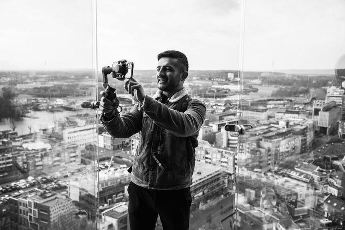 Vluchteling Kamiran op de Eusebius-toren met Arnhem op de achtergrond. Foto maakt deel uit van het boek dat fotograaf Bernard de Graaf over zijn leven maakte.