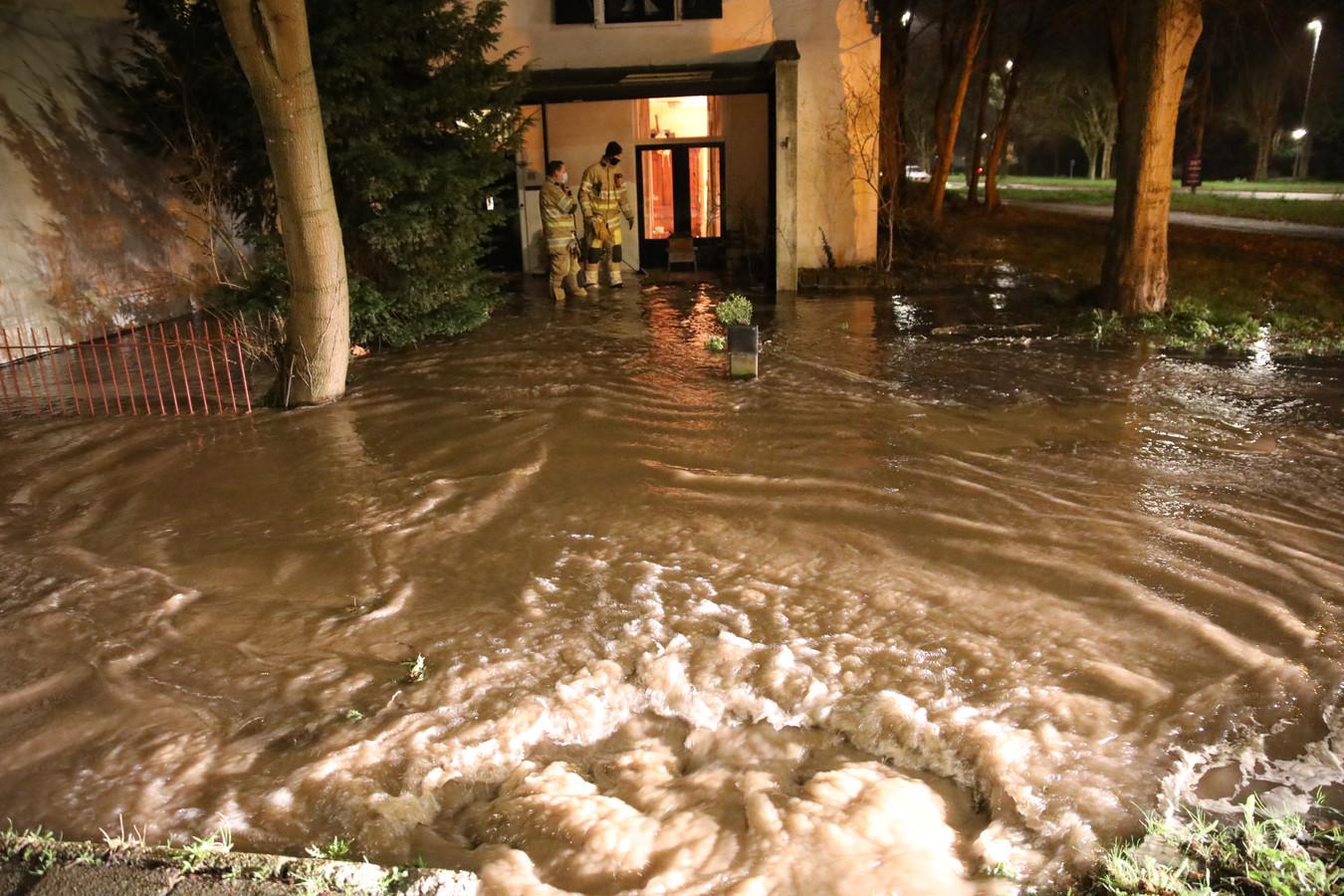 Water kolkt omhoog uit de gesprongen waterleiding langs de Utrechtseweg in Zeist en stroomt de naastgelegen woning binnen.