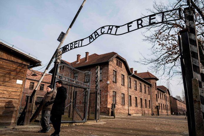 Holocaust-overlever Johnny (Ephroim) Jablon (links) loopt onder de poort van vernietigingskamp  Auschwitz-Birkenau door, waar hij tijdens de Tweede Wereldoorlog gevangen werd gehouden. Archiefbeeld.