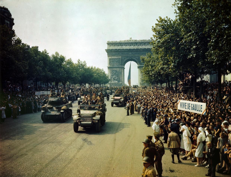 Franse patriotten verwelkomen de Amerikaanse bevrijders op de Champs Elysées in Parijs, 25 augustus 1944. Beeld Universal Images Group via Getty