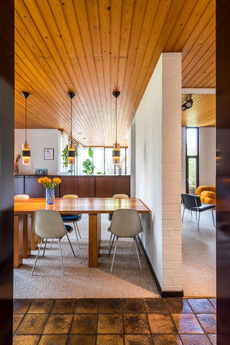 Rond de eettafel van Cassina staan Eames-stoelen met zittingen in Yves Klein-blauw. Zowel de tafel als de verlichting erboven kon het koppel overnemen van de vorige bewoonster, modeontwerpster Veronique Branquinho.  Beeld Luc Roymans