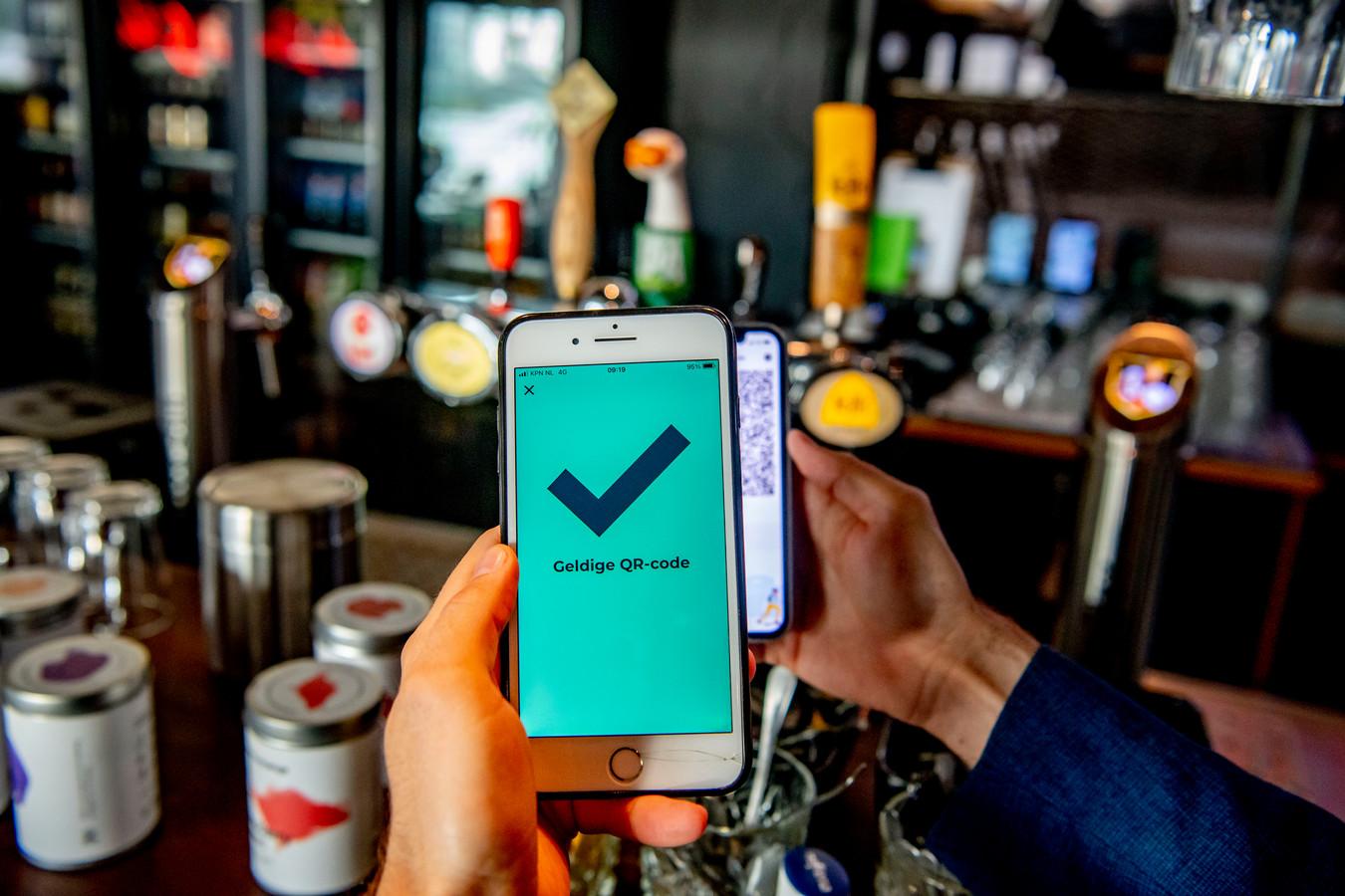 Een mobiele telefoon met de QR-code via de app CoronaCheck. Een coronabewijs betekent dat iemand gevaccineerd moet zijn, of hersteld van het virus of recent negatief getest.