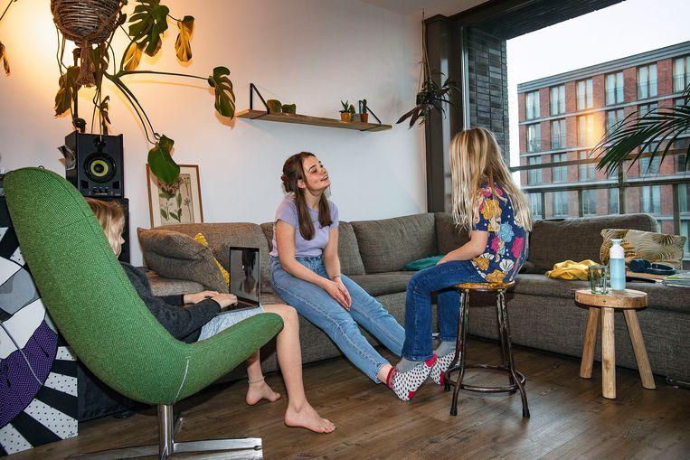 De kinderen worden opgevangen door de oppas in de woonkamer, terwijl de ouders werken in de slaapkamer. Beeld Guus Dubbelman / de Volkskrant