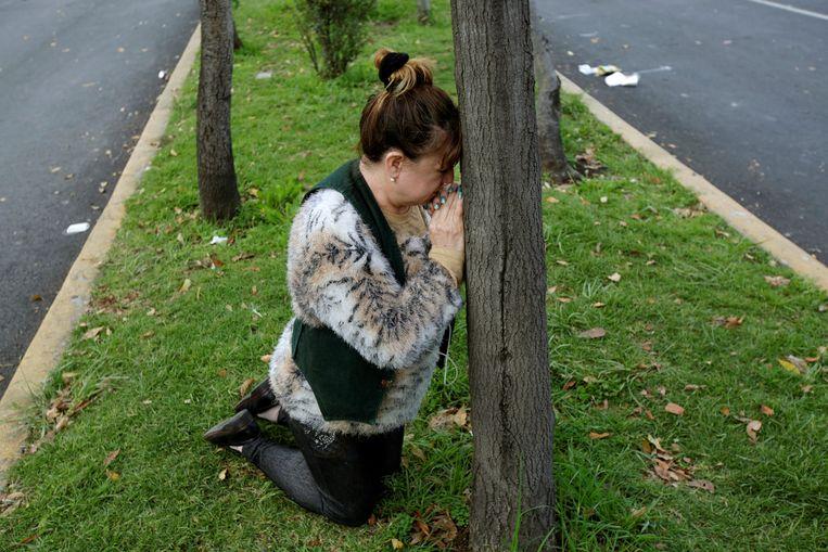 Een vrouw bidt na de nieuwe aardbeving.