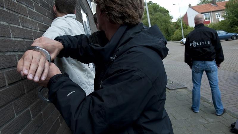 Een politieagent arresteert een verdachte. Foto ter illustratie.