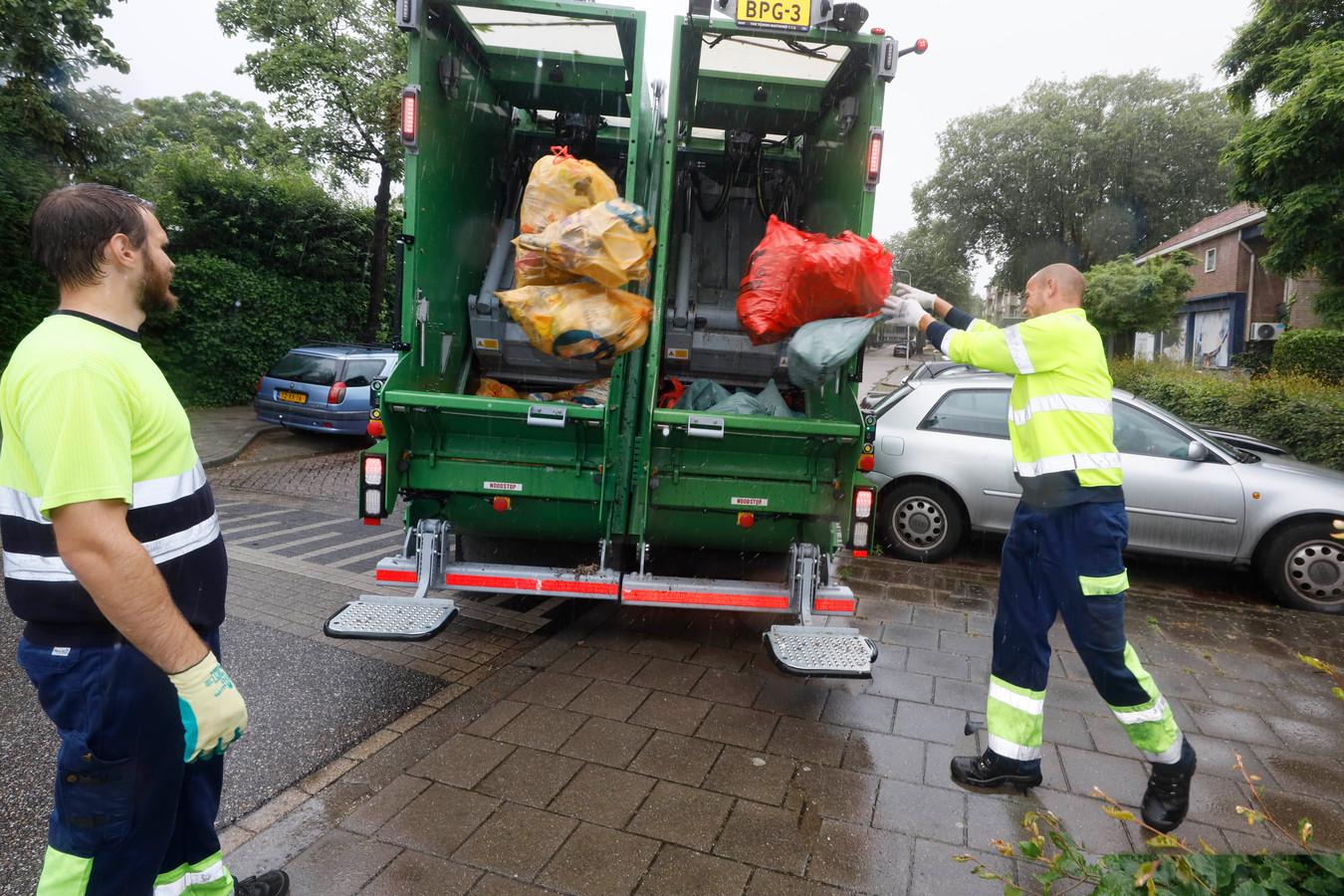 Medewerkers van DAR bij de vuilniswagen die het afval gescheiden afvoert: links plastic, rechts restafval.