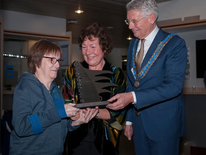 Riekie Brugmans (l) ontvangt uit handen van burgemeester Toon van Asseldonk van Overbetuwe de vrijwilligersprijs 2017.