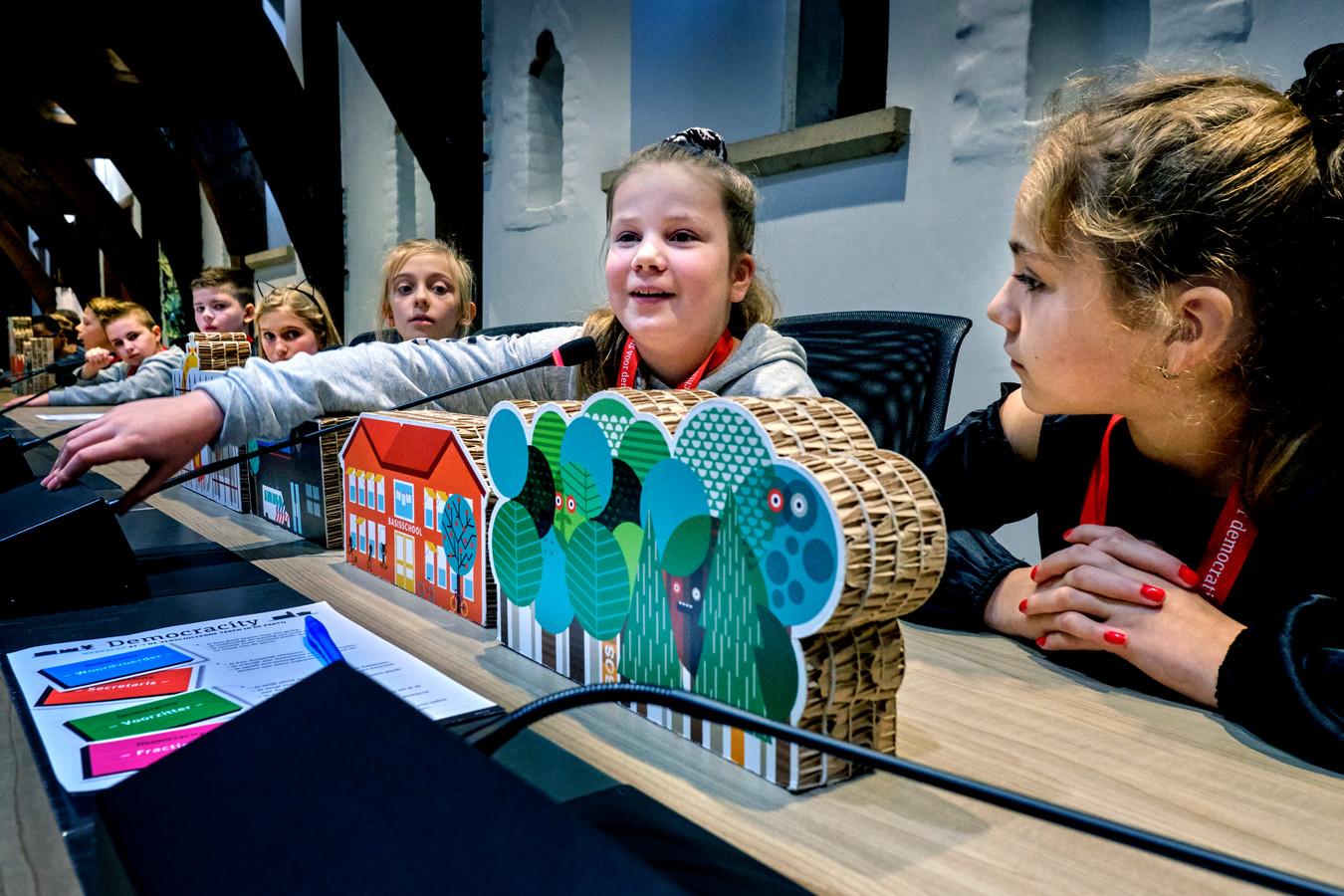 Scholieren spelen Democracity in de raadzaal van Dordrecht.