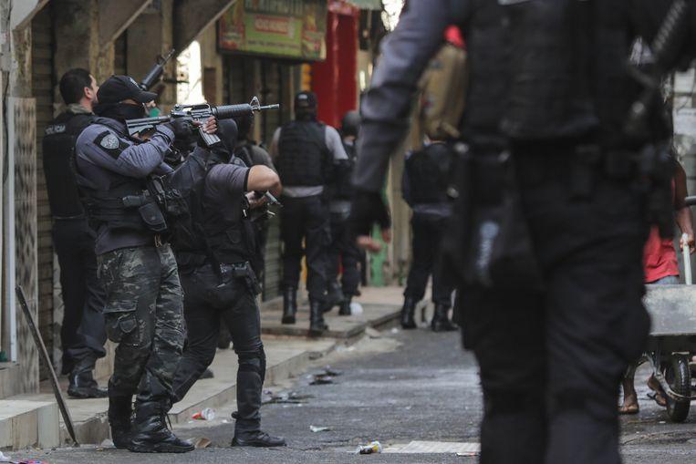 Zwaarbewapende politie-eenheden tijdens de actie in de wijk Jacarezinho in de Braziliaanse stad Rio de Janeiro. Beeld EPA