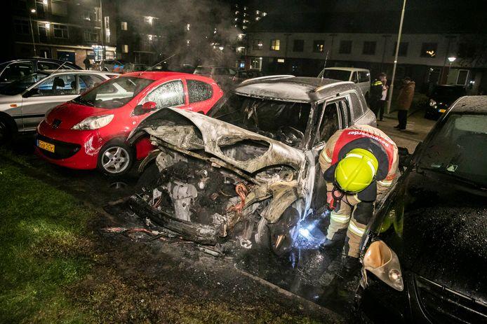 Een brandweerman inspecteert de auto na het blussen van de brand aan de Dedelstraat in Arnhem.
