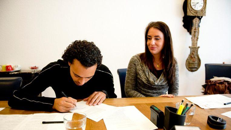 Een jong stel tekent de papieren voor hun nieuwe huis bij de notaris. Beeld anp