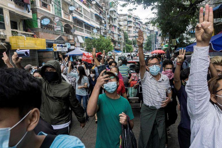 Betogers in de grootste stad van Myanmar, Yangon, maken een gebaar met drie vingers. Dat is het symbool geworden van het verzet tegen de militaire junta van Myanmar, die afgelopen februari de macht greep. Beeld AFP