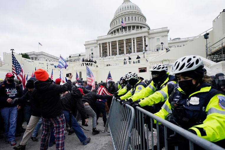 Trump-aanhangers breken door een barricade aan het Capitool. Beeld AP