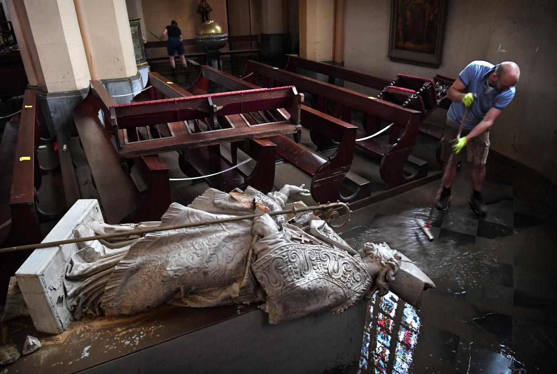 Een man veegt water uit de Oude Kerk in Valkenburg. Het gebedshuis raakte afgelopen week flink beschadigd. Beeld Marcel van den Bergh / de Volkskrant