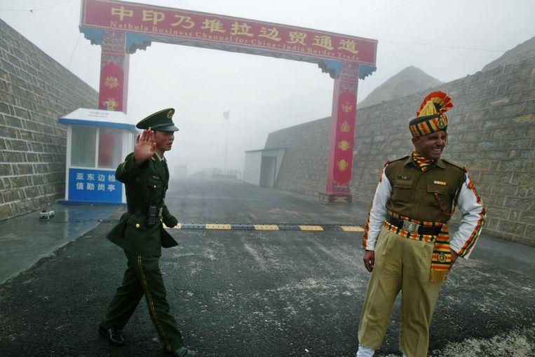 Een Chinese soldaat (l) en zijn Indiase collega (r) bij de grens tussen beide landen in de Himalaya.  Beeld AFP