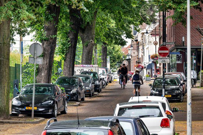 Parkeren op de Sonsbeeksingel langs het spoor in Arnhem: elke plek is bezet, soms wijken automobilisten uit naar plaatsen waar parkeren niet is toegestaan. Op de achtergrond rechts horecagelegenheid CASPAR.