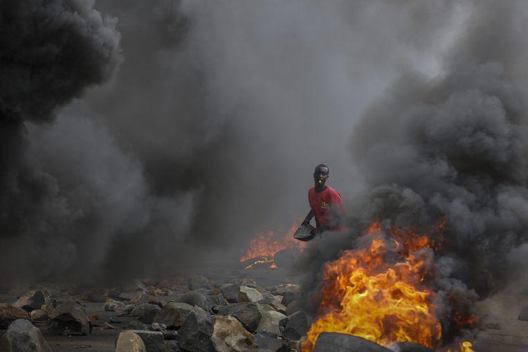 Een demonstrant gooit met een steen tijdens massale demonstraties tegen de derde ambtstermijn van president Nkurunziza in mei. Beeld EPA
