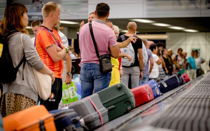 Reizigers wachten op hun koffers bij een bagageband op de luchthaven Schiphol.