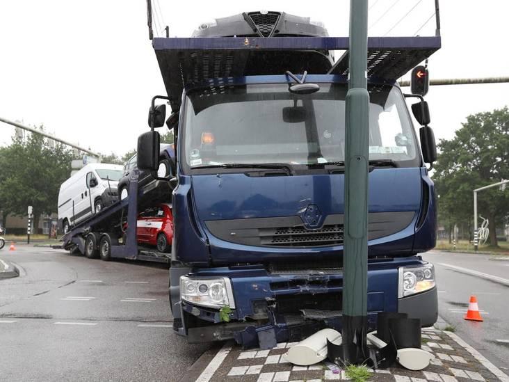 Vrachtwagen geladen met auto's rijdt tegen lantaarnpaal in Oosterhout