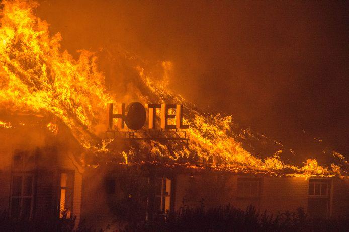 Het grote, rieten dak van het hotel wordt verzwolgen door het vuur. Om te voorkomen dat de brand oversloeg op andere rieten daken, werden de omliggende panden ook natgehouden door de brandweer.