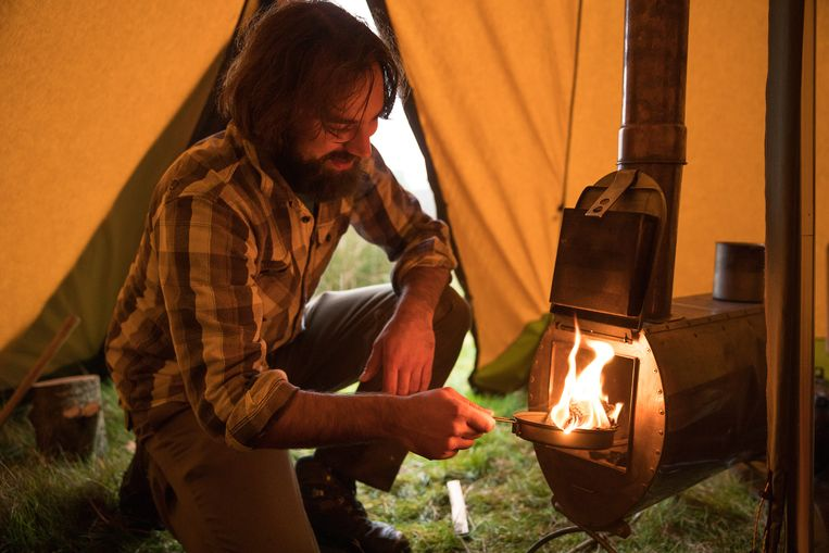 Koen Arts steekt de kachel in zijn tent aan. Beeld Otto Kalkhoven