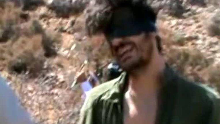 Een screenshot van een video met de Amerikaanse journalist Austin Tice die is verdwenen in Syrië. De andere mannen in de video zijn vermoedelijk zijn ontvoerders. Beeld AFP