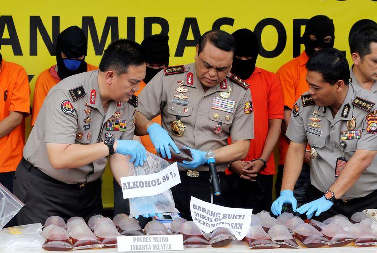 De politie controleert grote hoeveelheden in beslag genomen alcohol tijdens een persconferentie in Jakarta. Beeld AP