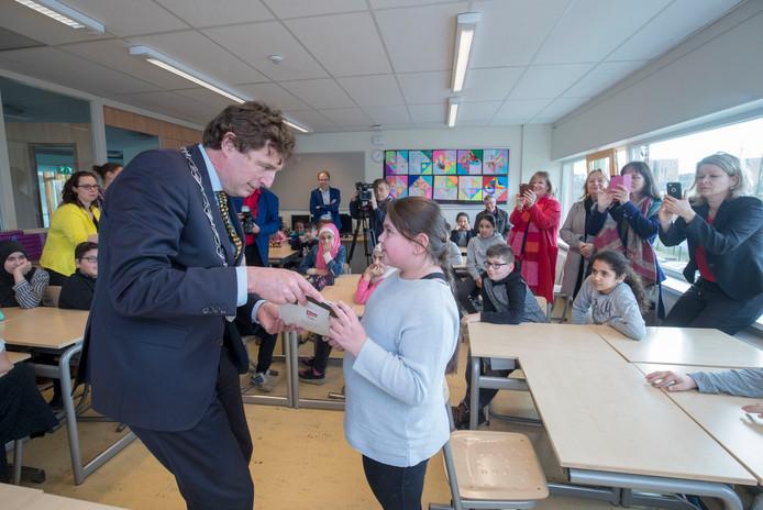 Burgemeester René Verhulst overhandigt het eerste exemplaar van Als ik de baas was dan... aan Suda uit groep 7/8 van De Bongerd in Ede.