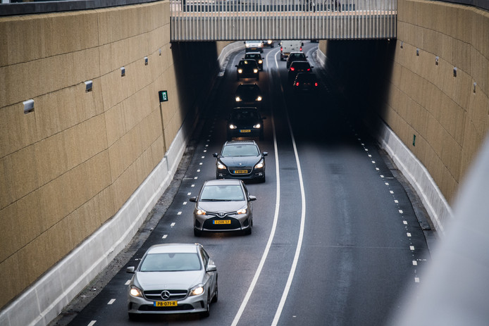 Automobilisten rijden de tunnel in.
