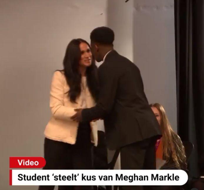 Een ondeugende student beklom tijdens Meghan Markles speech op Internationale Vrouwendag het podium en gaf haar een kus en een knuffel.
