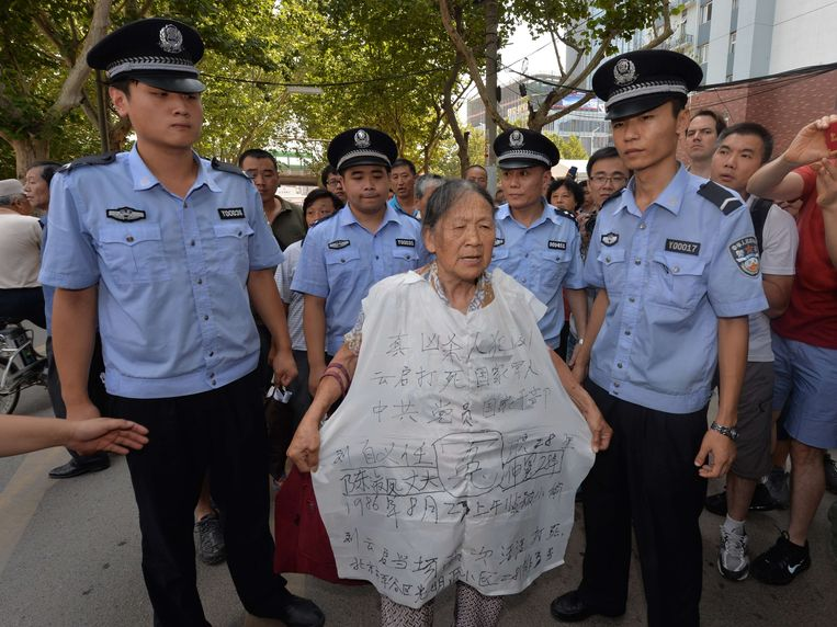 Police surround a protester (C) outside the Intermediate People's Court where disgraced politician Bo Xilai will soon go on trial in Jinan, Shandong Province on August 21, 2013.  Once one of China's highest-flying politicians, Bo Xilai will find himself in a criminal dock on August 22 on trial for bribery and abuse of power in the country's highest-profile prosecution in decades. His downfall began when a British businessman was found dead in a hilltop hotel room. As the drama finally nears its conclusion, the Communist Party is touting it as proof of its intent to crack down on corruption.      AFP PHOTO / Mark RALSTON Beeld AFP