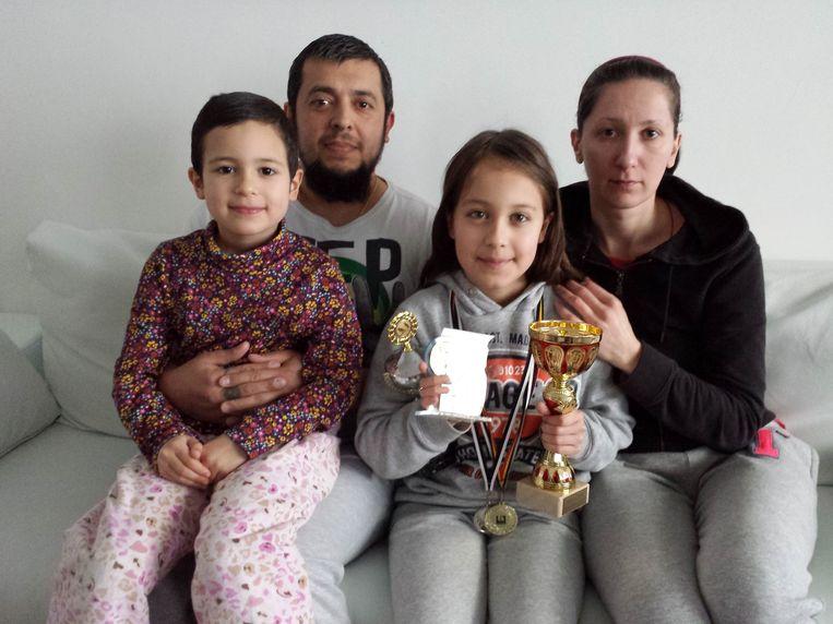 Karina met haar schaaktrofeeën en medailles, samen met haar zusje en ouders.