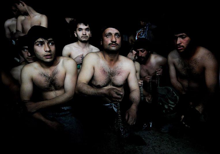 Sjiietische mannen houden hun kettingen vast voordat ze deelnemen aan het festival Ashura. Hierbij kastijden zij zichzelf om het tragische lot van Hussein, de kleinzoon van Mohammed, die in het jaar 680 is omgekomen bij de slag om Kerbala.  Beeld AFP