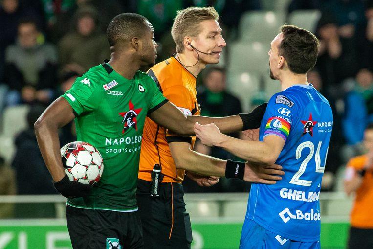 AA Gent-middenvelder Kums (r.) gaat verhaal halen bij ref Visser na een afgekeurde goal. Dabila maant aan tot kalmte. Beeld BELGA