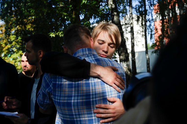 Mensen knuffelen elkaar na te zijn vrijgelaten uit het detentiecentrum in Minsk. Beeld AP