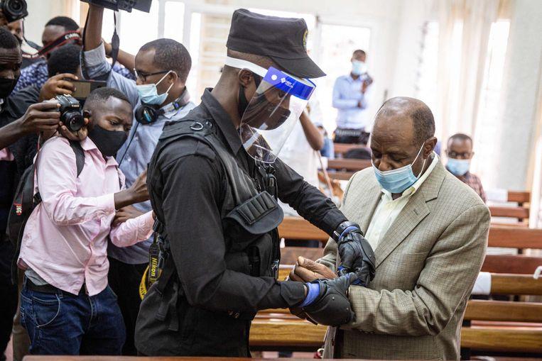 Paul Rusesabagina (rechts) krijgt handboeien om nadat hij eind 2020 is voorgeleid in Kigali. Vandaag werd hij schuldig bevonden aan terrorisme. Uit protest woonde hij de zitting nu niet bij. Beeld AFP