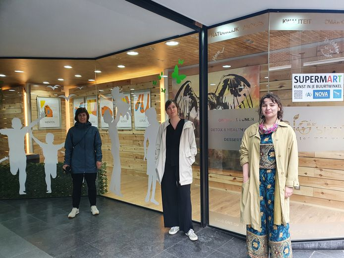 Districtsschepen van Cultuur Femke Meeusen (Groen), Margot van den Berghe (Nova) en Denisa Teglas aan de vitrine van de nieuwe BioSpace, waar verschillende werken twee maanden lang staan te pronken.