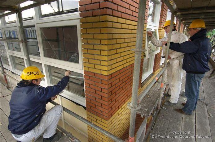 Leerlingen van het SPOS (schildersopleiding) aan het werk bij hun eigen nieuwbouw achter de bestaande locatie aan Sportlaan Driene.