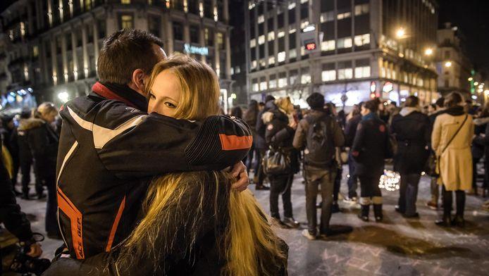 Deux jeunes gens se réconfortent l'un l'autre devant la Bourse de Bruxelles après les attentats qui ont meurtri la capitale belge.