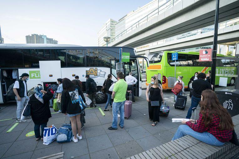 Vakantiegangers stappen bij het Sloterdijkstation in Amsterdam op de Flixbus. Veel reizigers kiezen voor de bus als goedkoper alternatief voor vliegtuig of trein.  Beeld ANP