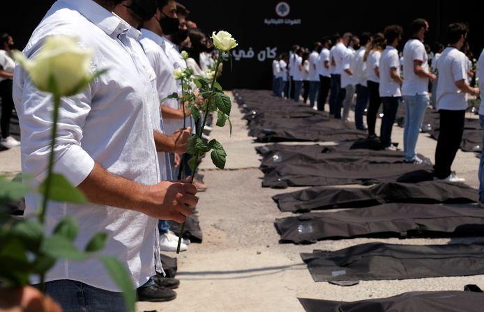 Des étudiants affiliés aux Forces libanaises tiennent des roses blanches et se tiennent à côté de sacs mortuaires en mémoire des victimes de l'explosion du port de Beyrouth de l'année dernière, alors que le Liban marque le premier anniversaire de l'explosion à Beyrouth.