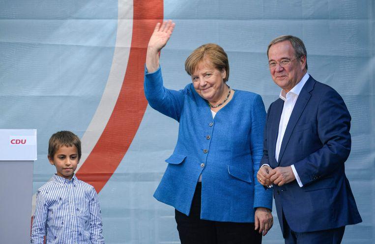 Angela Merkel samen met haar beoogde opvolger Armin Laschet, gisterenavond bij de slotbijeenkomst van de CDU. Beeld AFP