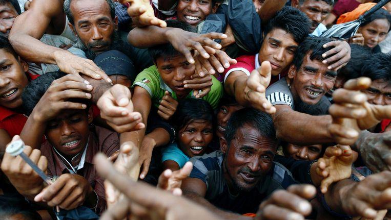 Rohingya-vluchtelingen in Bangladesh strekken hun handen uit naar hulpgoederen in een vluchtelingenkamp. Beeld reuters