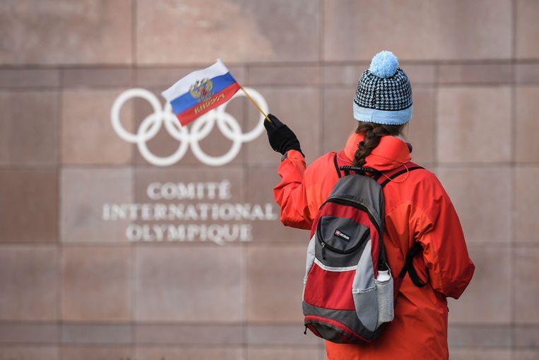 Een vrouw zwaait met de Russische vlag voor het hoofdkwartier van het IOC in Lausanne. Beeld AFP