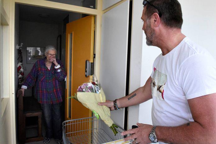 ANBO-ambassadeur John de Wolf boeketten uitdeelt aan thuiswonende ouderen.