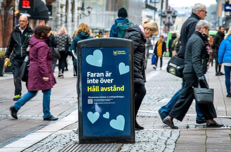 In het Zweedse Uppsala zijn de winkels gewoon open, maar op de prullenbakken wordt gewaarschuwd: corona is nog niet voorbij, bewaar afstand.  Beeld AP